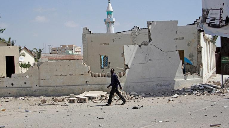 Man går förbi ruiner av hus i Mogadishu. Arkivbild.