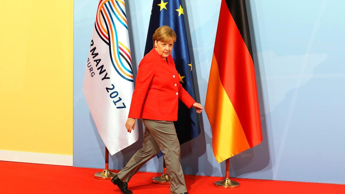 Kvinna går framför flaggor.