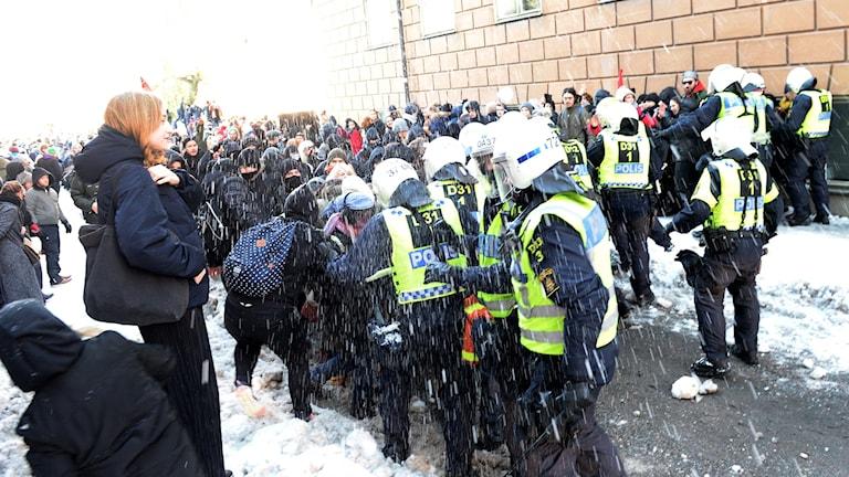 Polisen håller undan motdemonstranter när Nordiska motståndsrörelsen samlas för sin demonstration i Kungsträdgården för att gå till Mynttorget i Stockholm