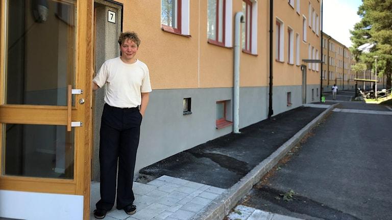 Unga man i mörka byxor och vit tröja står intill en bort till bostadshus.