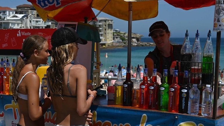 Tjejer som köper dricka på Bondi Beach.