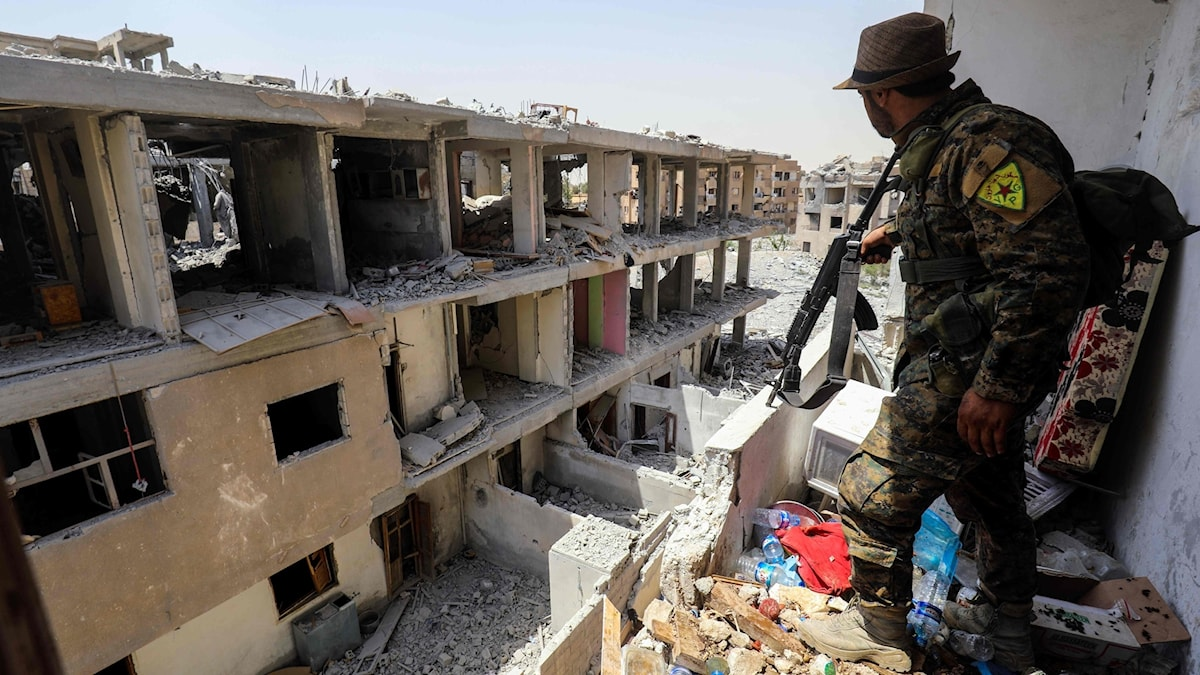 En soldat står i ett raserat hus.