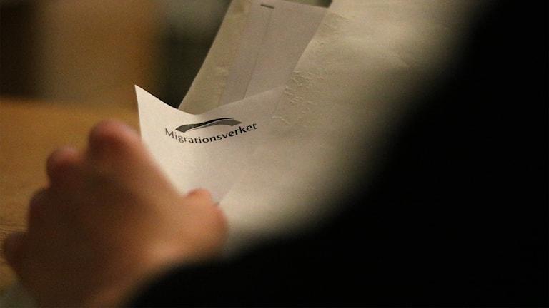 Migrationsverkets logotyp på papper i kuvert.