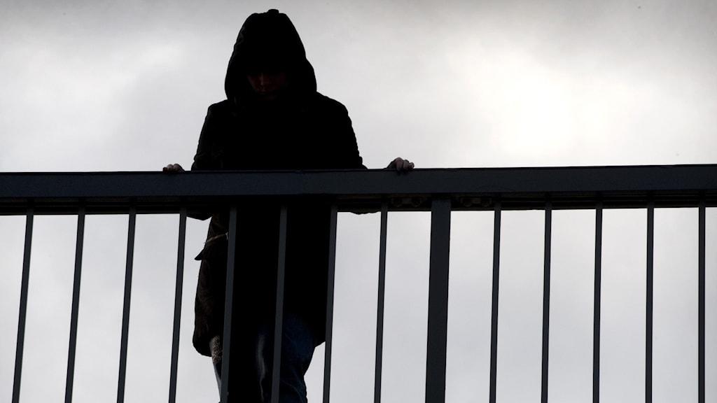kvinna står vid bro