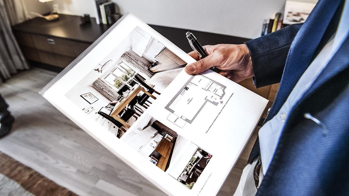 En person i kavaj håller ett informationsblad om en bostad till försäljning.