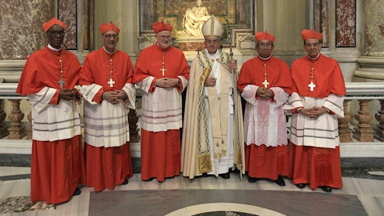 Fem äldre män i röda dräkter på rad och en äldre man i mitten med vita kläder och en hög hatt.