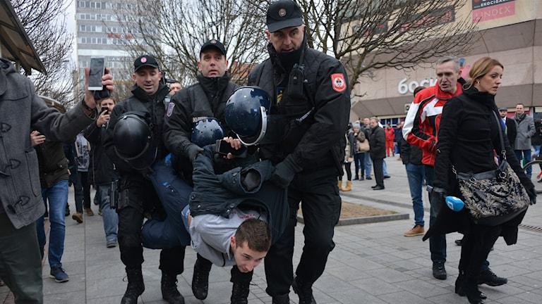 Person blir gripen och bortburen av polis.
