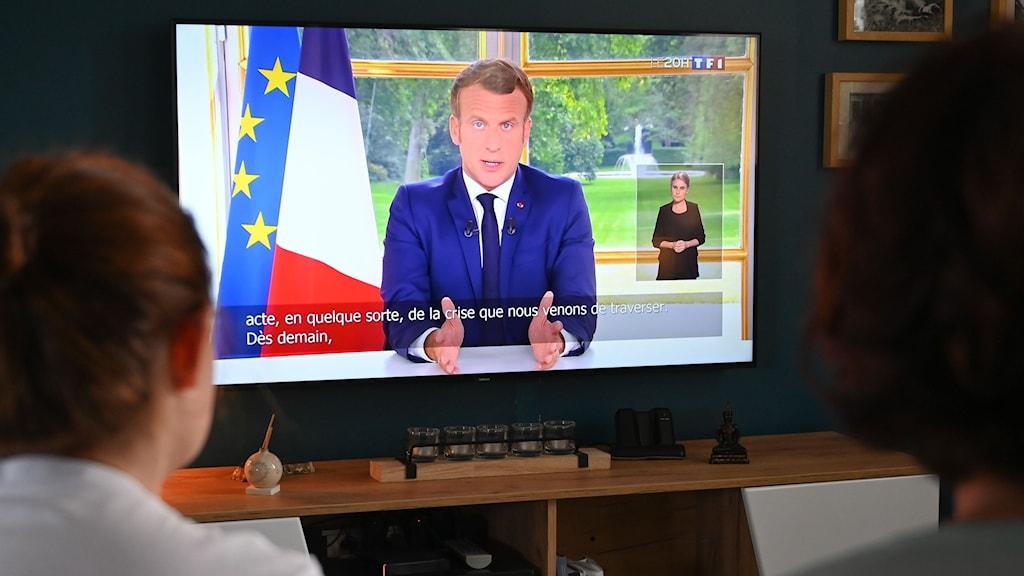 Familj som tittar på tv när Frankrikes president håller tal.