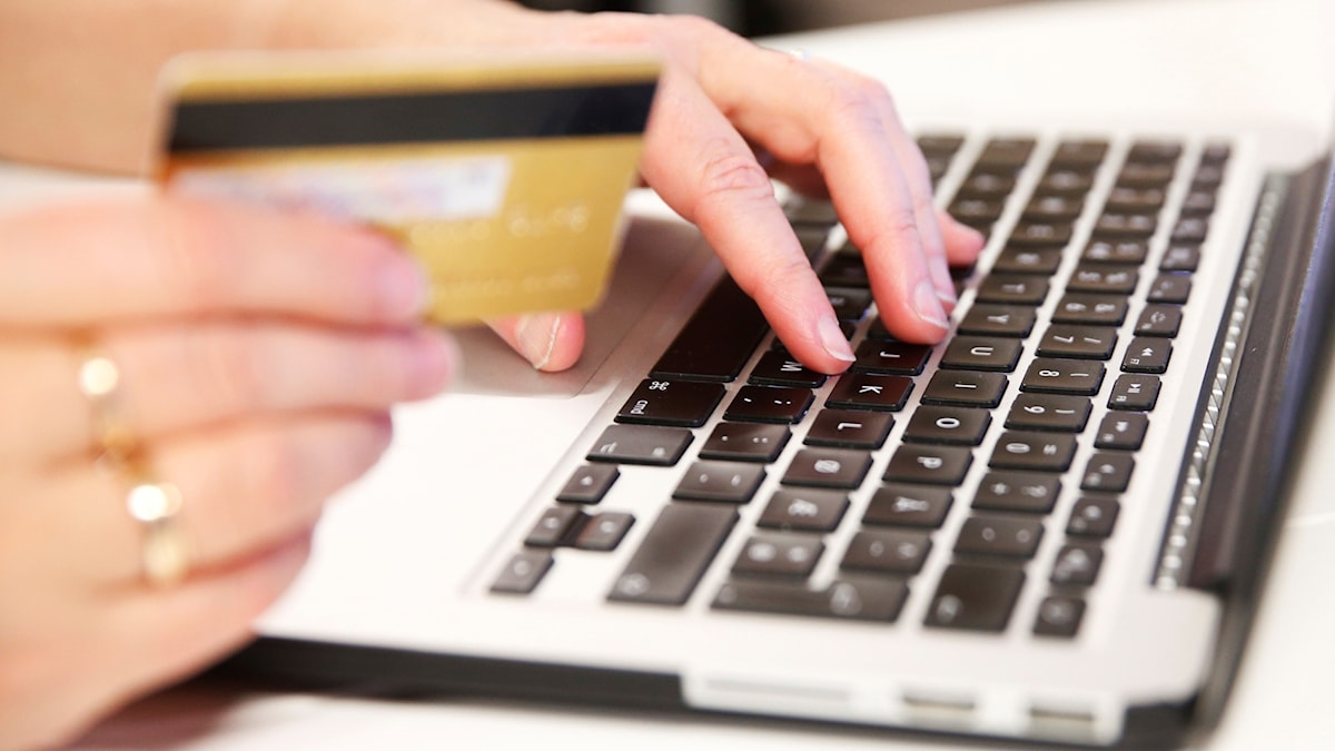 Person sitter vid laptop med ett kreditkort.