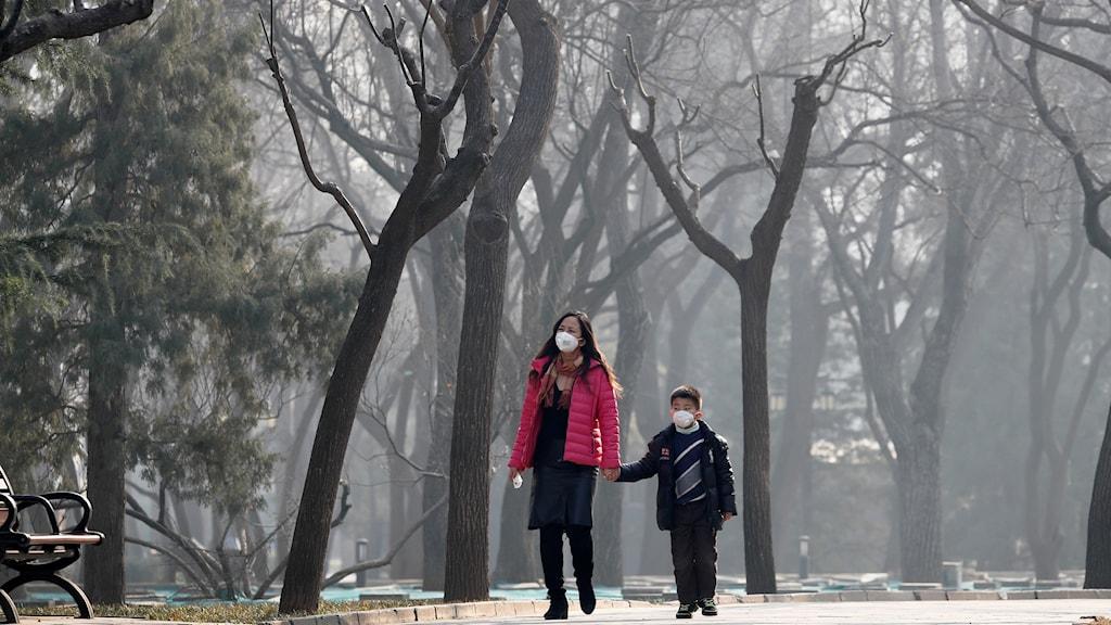 Kvinna och barn med mask för ansiktet
