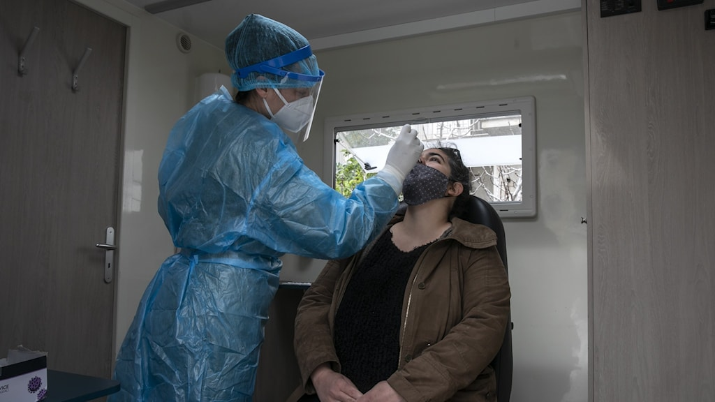 Läkare med skyddskläder utför provtagning av person med munskydd.
