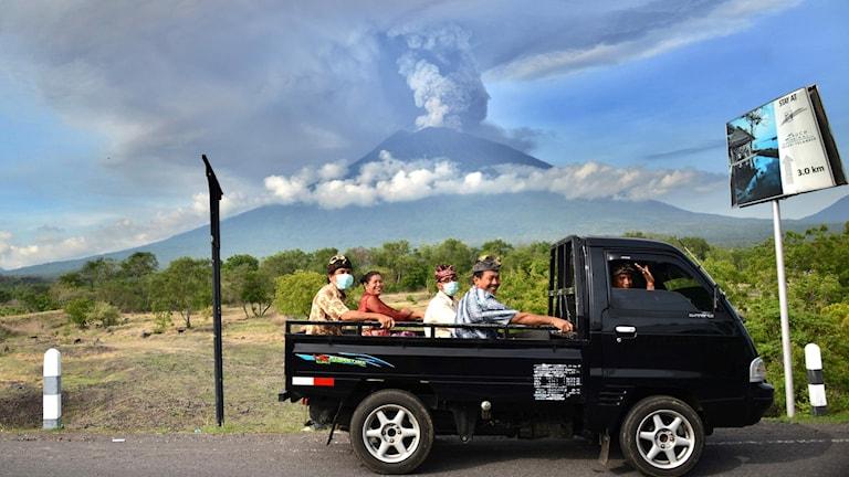 Människor sitter på en lastbil, i bakgrunden syns en vulkan som det kommer rök ur.