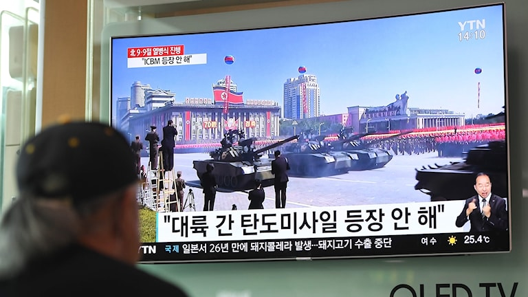 En man tittar på rapporteringen från militärparaden på Seouls tågstation i Sydkorea.