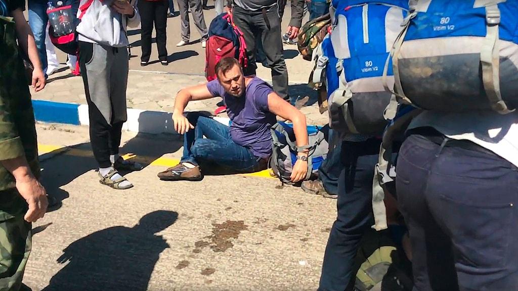 Oppositionsledaren Aleksej Navalny försöker resa sig upp efter attacken.