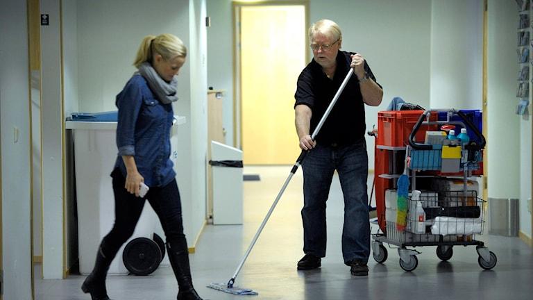 Äldre man städar golv