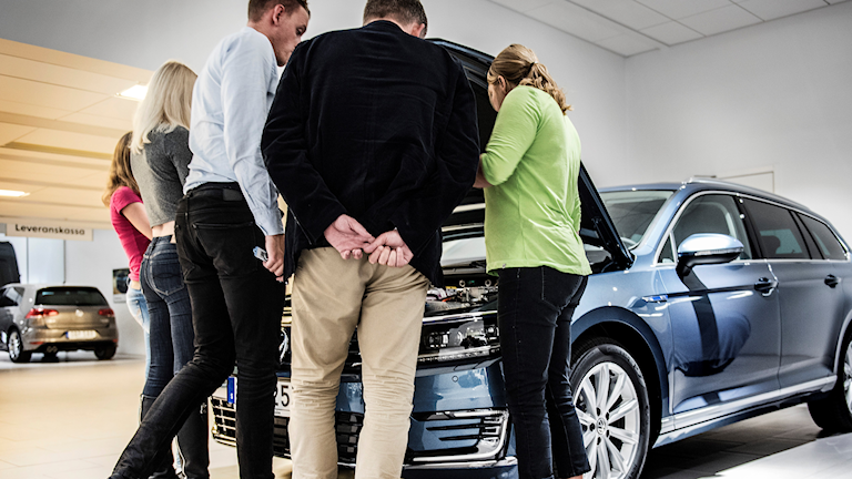 En familj tittar på en Volkswagen