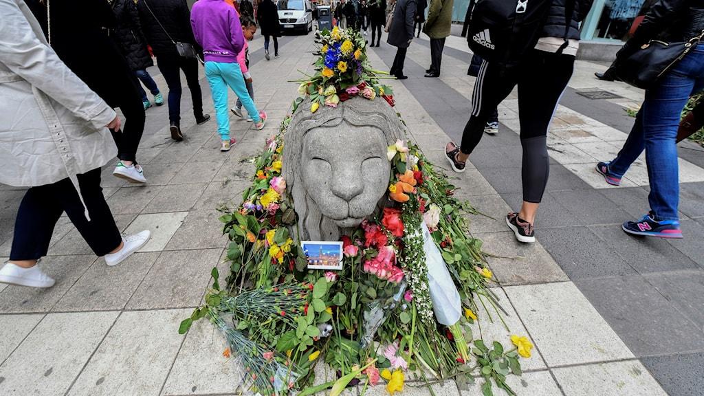 Blommor på ett lejon av betong.
