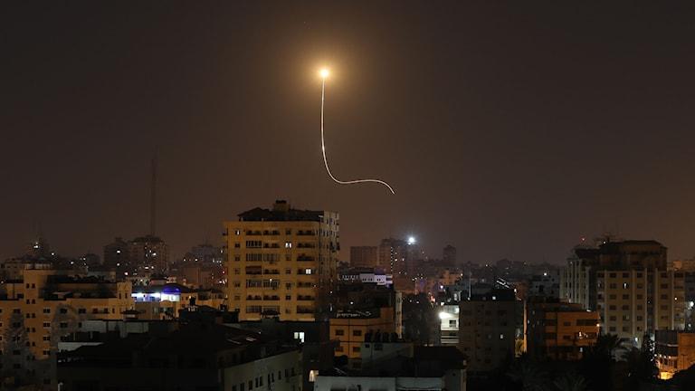 Raket mot mörk himmel över stad.