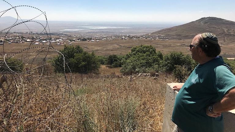 Bosättaren Dubi Hadar blickar ut över flyktinglägren i Syrien från de ockuperade Golanhöjderna
