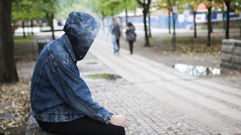 Bortvänd kille med huvtröja och jeansjacka som röker.