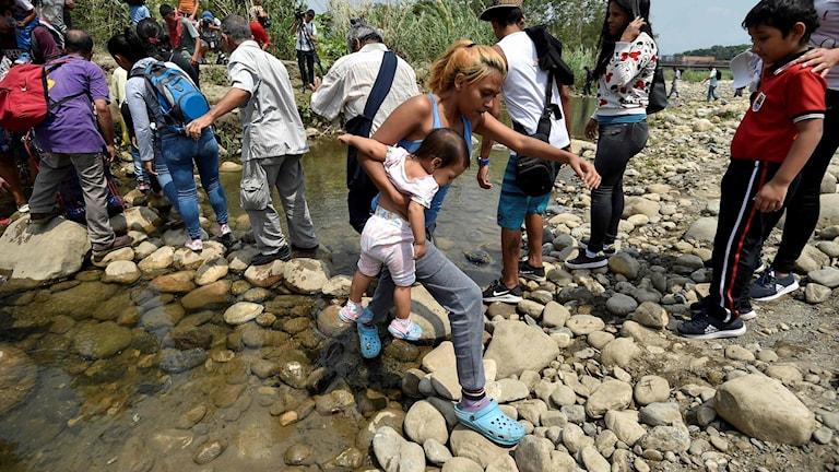 Människor tar sig igenom floden Tachira på vägg till Colombia. Foto: Luis Robayo/TT.