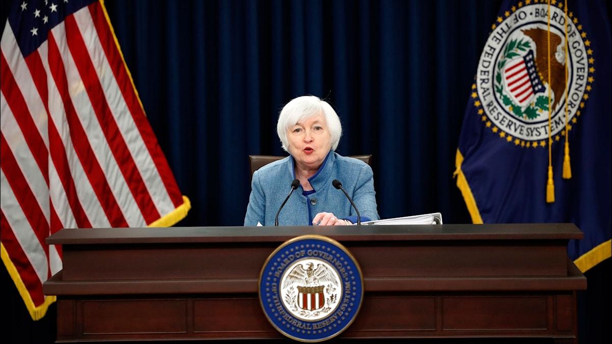 Fed-chefen Janet Yellen sitter vid ett skrivbord och talar