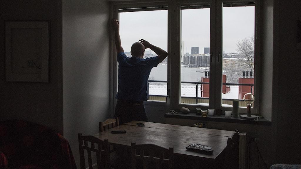 man står framför fönster i mörk lägenhet