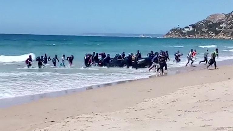 En stor gummibåt med människor når stranden.
