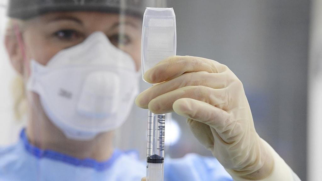Vårdpersonal i skyddsutrustning förbereder en spruta för injektion.