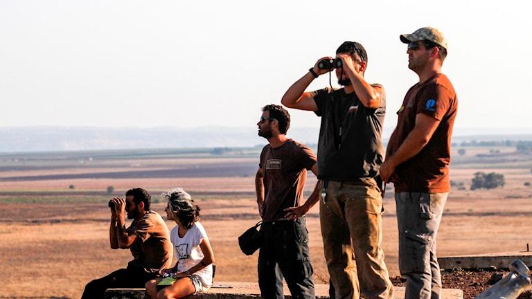 Israeler som befinner sig på Golanhöjden blickar ut över gränsen till Syrien.