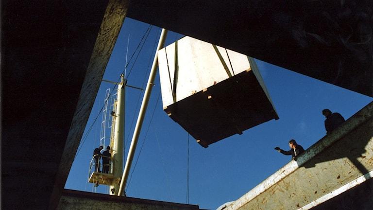 Stor box lastas i en hamn.