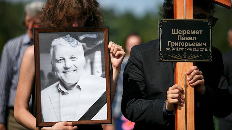 Närstående håller ett porträtt på Pavel Sheremet på hans begravning.
