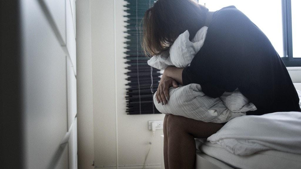 en kvinna som sitter på en säng.