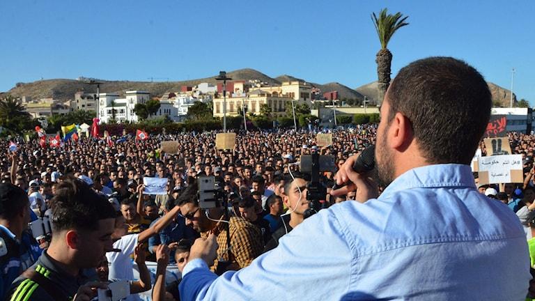 Bilder visar den Marockanske aktivisten Nasser Zefzafi framför en stor folksamling.