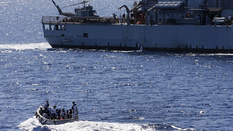 bild på migrantbåt och militärfartyg.