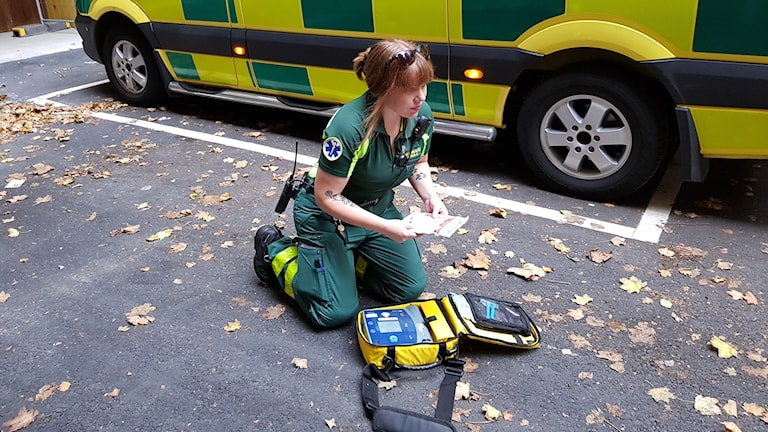 Ambulanssjukvårdare sitter på knä vid en hjärtstartare.