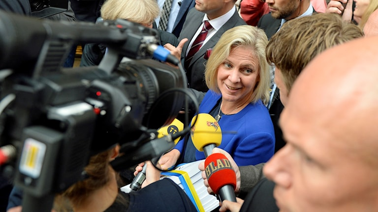 Finansminister Magnadela Andersson med budgeten, en trave papper inlindad i blågult band, omringad av reportrar.