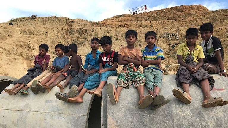 Pojkar sitter på ett betongrör