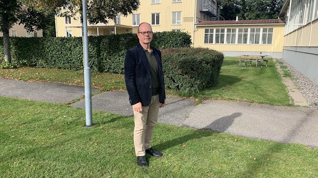 Rektorn Magnus Linder står på gräsmattan på Viskadalens folkhögskola.