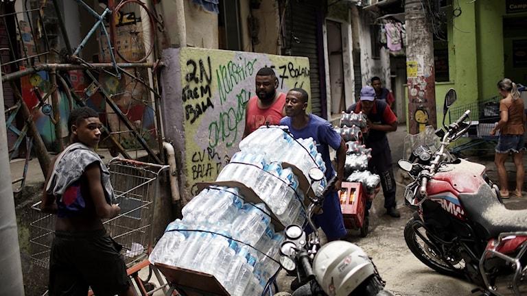 Man med vattenflaskor i en favela i Rio de Janeiro i Brasilien.
