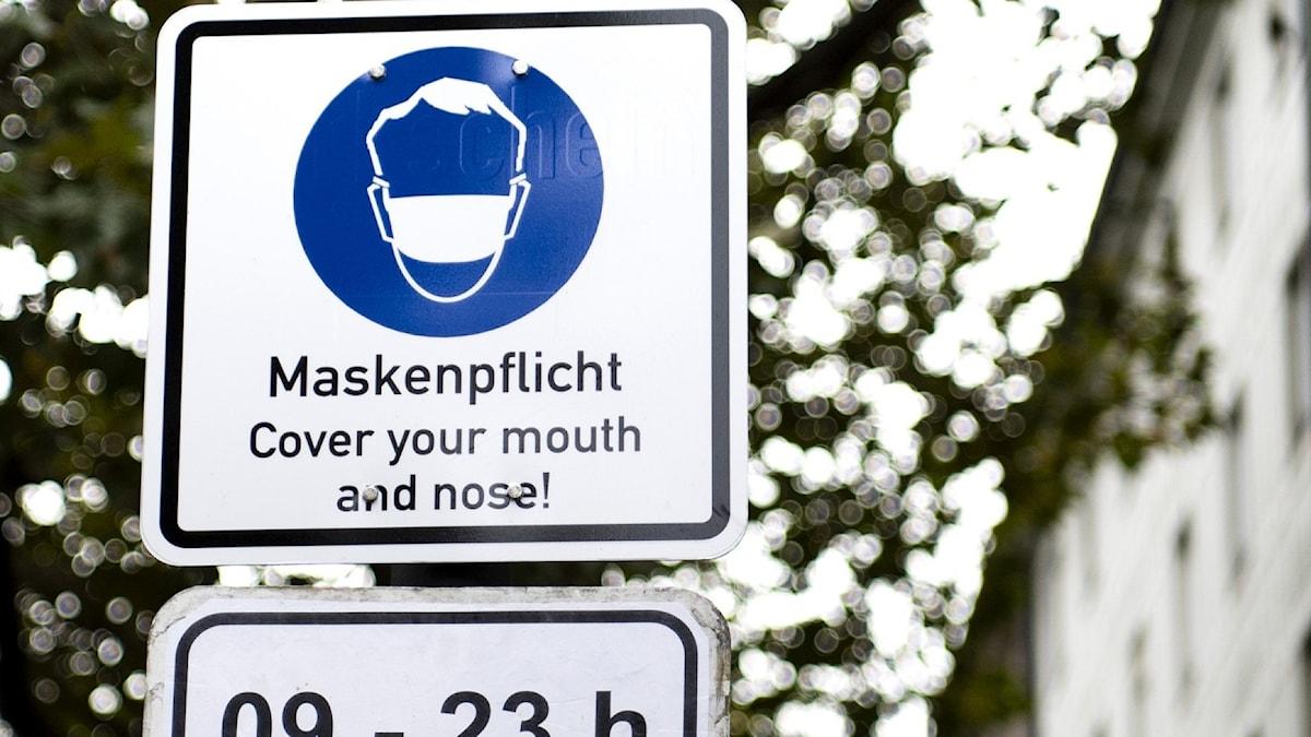 Skylt med ansiktsmask tysk text