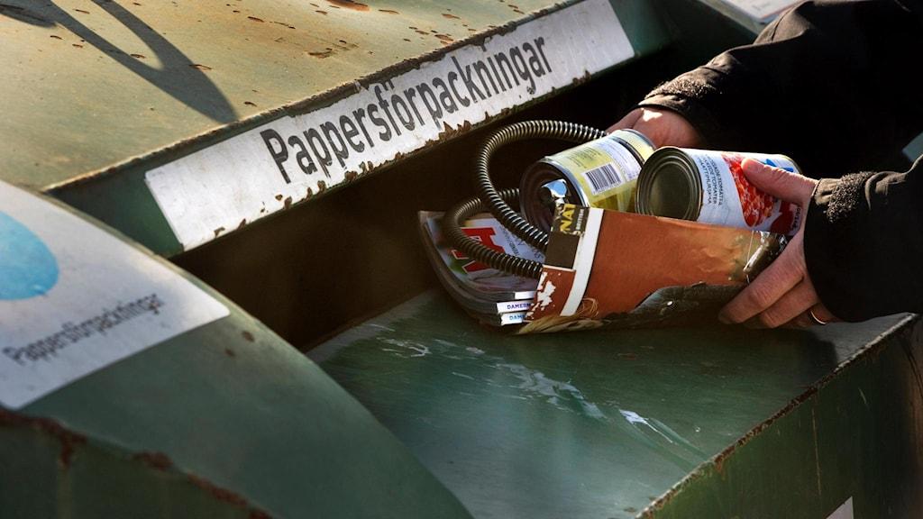 En man lägger metallförpackningar i ett återvinningskärl för papper.