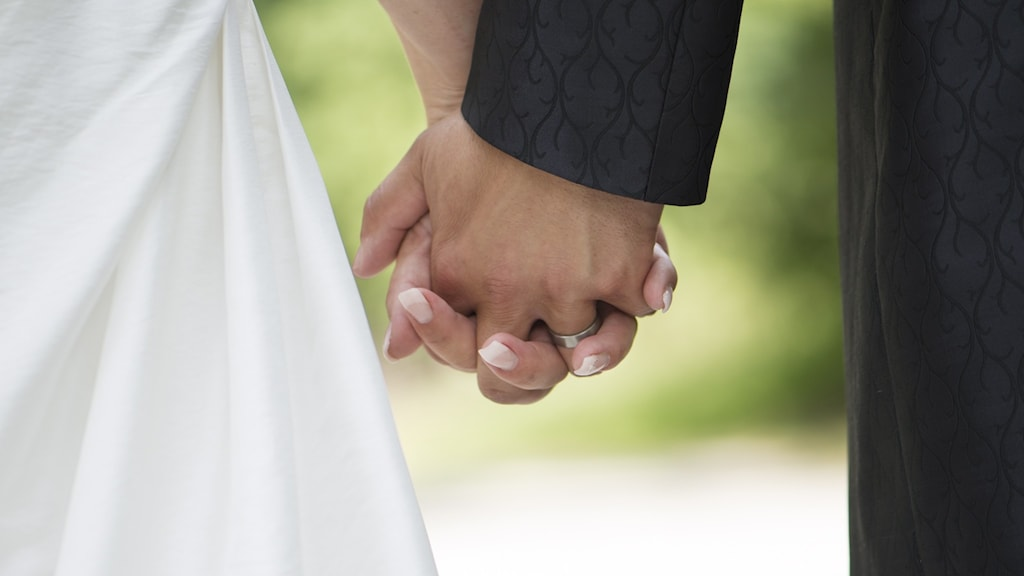 Ett brudpar går hand i hand.