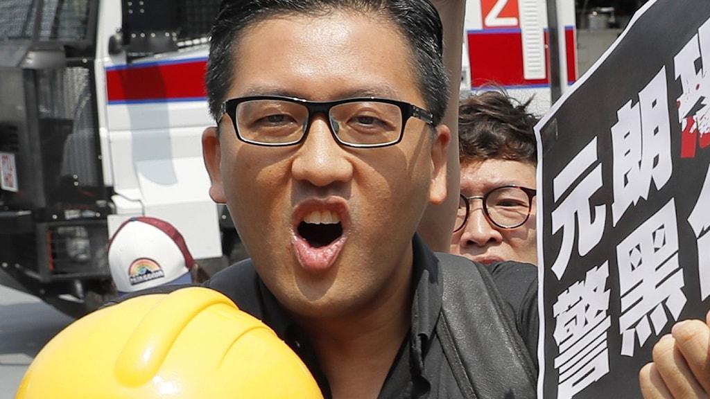 Parlamentarikern Lam Cheuk-ting filmar sig själv med sin mobil när polisen knackar på utanför hans hem tidigt i morse.