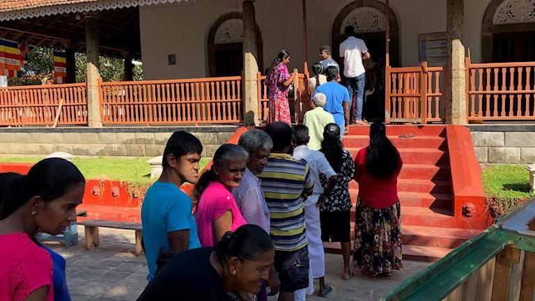 Personer utanför vallokalerna i Sri Lanka.