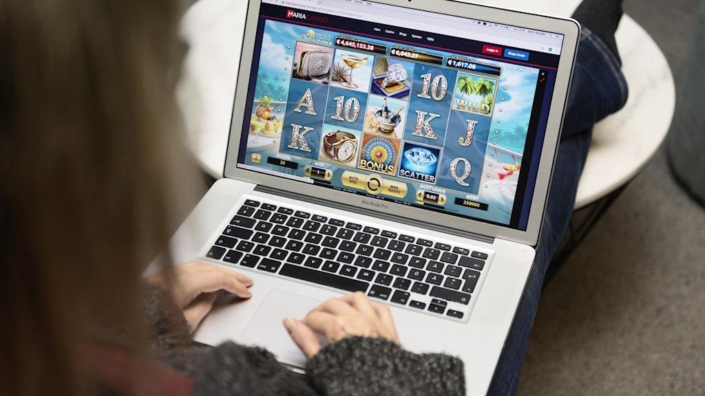 Kvinna spelar online kasinospel på bärbar dator.
