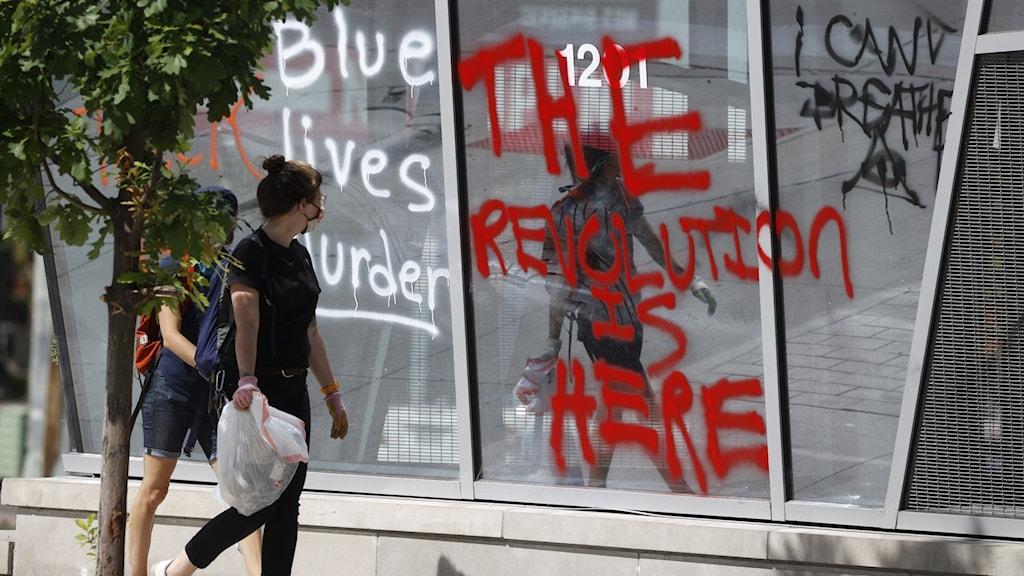 """Ett sönderslaget skyltfönster och någon som sprayat """"revolutionen är här""""."""