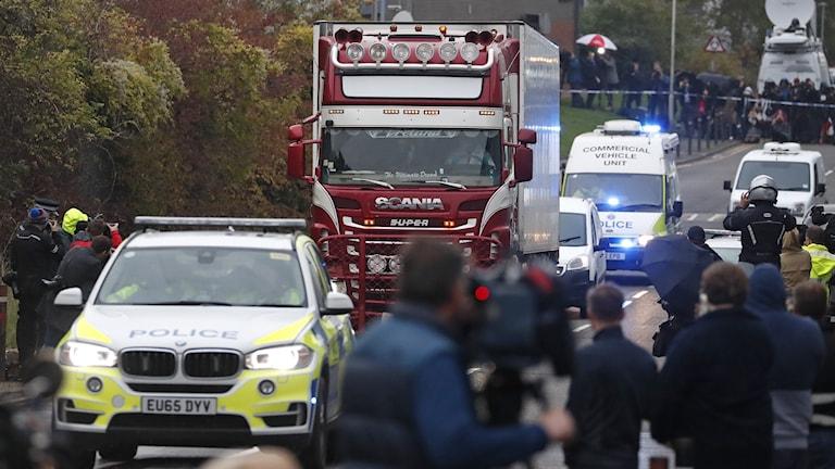 Polis eskorterar lastbilen i vilken 39 personer hittades döda.