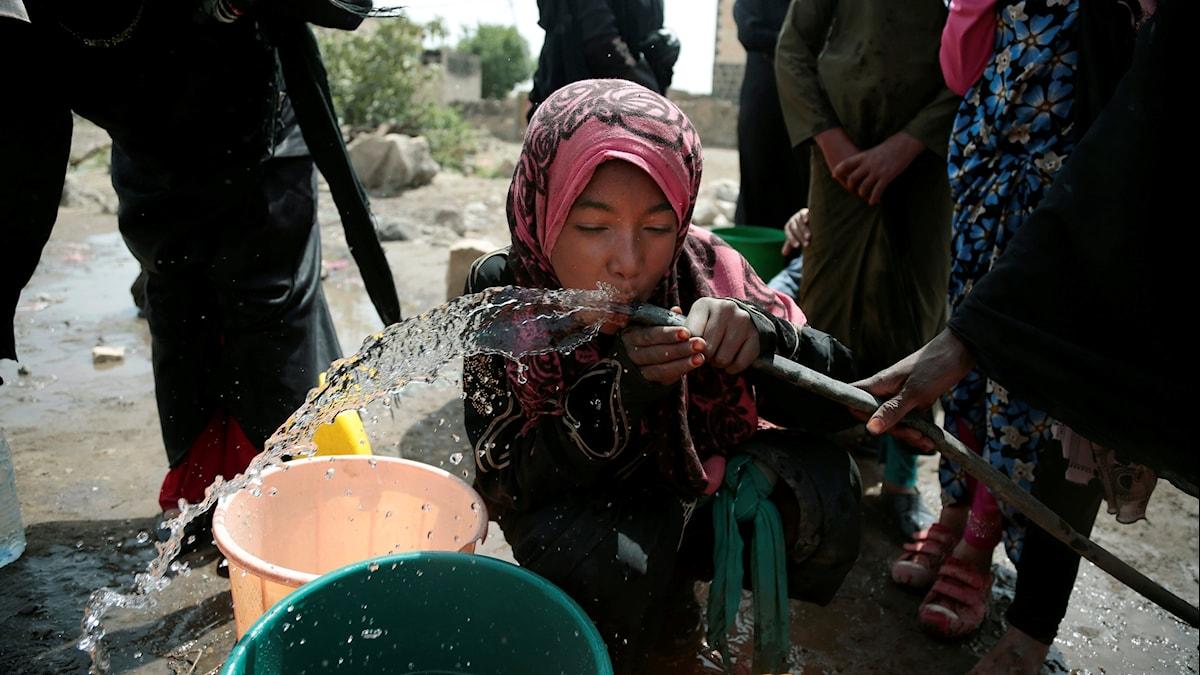 Flicka dricker vatten ur en slang.
