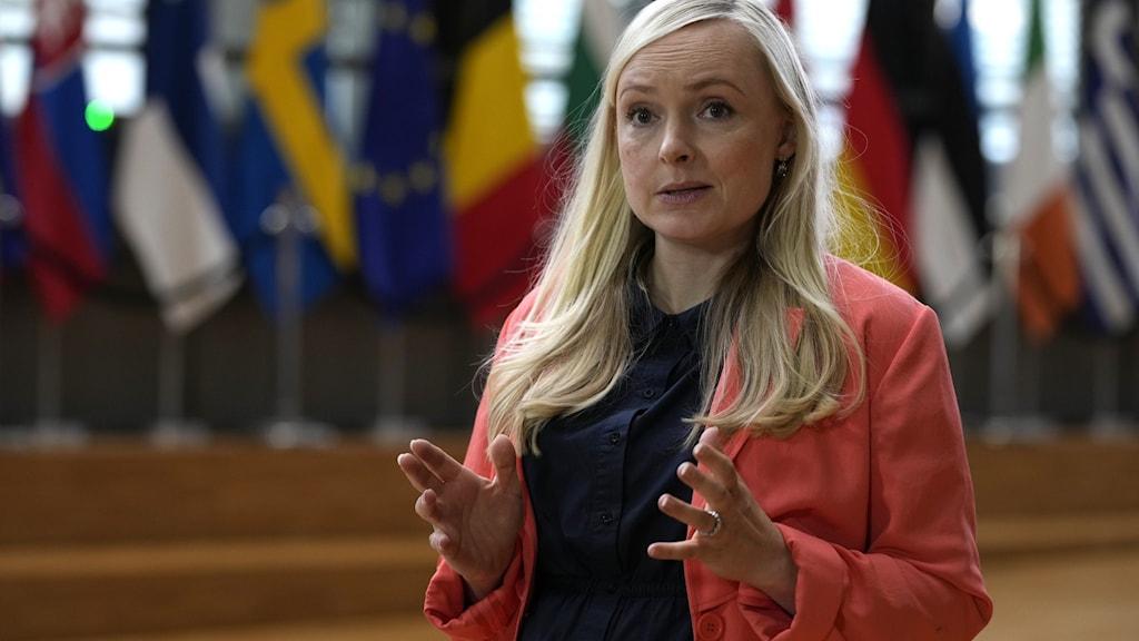 Finlands inrikesminister och finländska  miljöpartiets partiledare Maria Ohisalo som vill att kärnkraften klassas som hållbar eftersom kärnkraft kan ersätta fossila bränslen. Hon har långt blont hår mörkblå tröja och ljusröd kavaj. Står framför EU-ländernas fanborg.